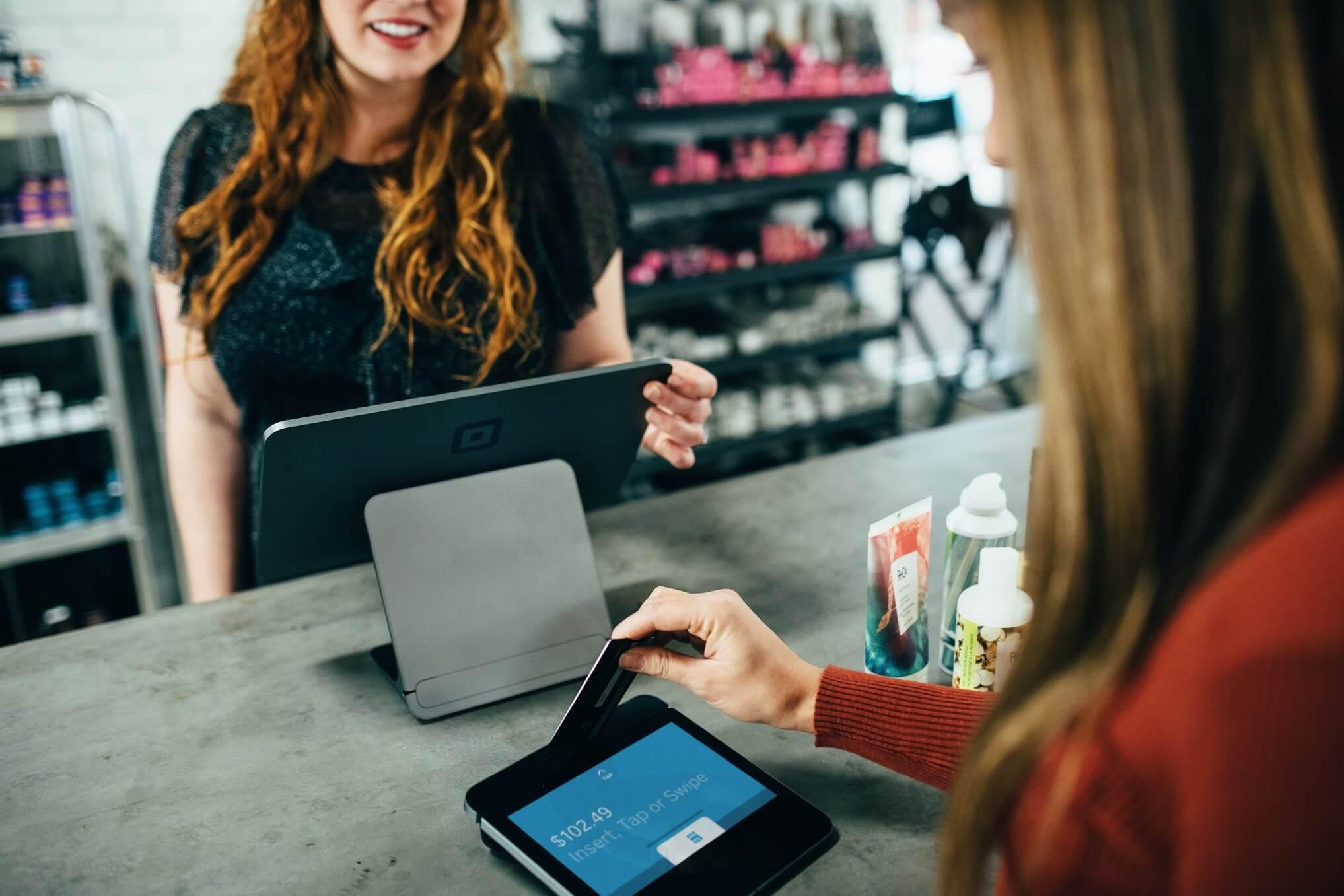 Una mujer paga la compra en una tienda con su tarjeta de crédito